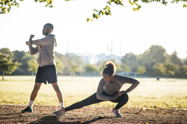 Couple stretching before a run in park